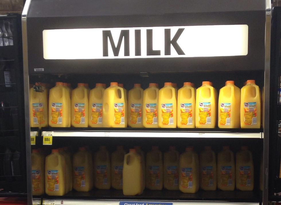 Cooler of Orange Juice labeled Milk